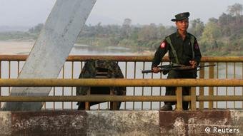 A Myanmar government soldier stands guard on Balaminhtin bridge over the Irrawaddy River near the city of Myitkyina in the north of the country after months of renewed fighting between government troops and the Kachin Independence Army, or KIA, February 22, 2012. (Photo: REUTERS/Strinter)