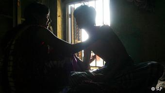 An Indian sex worker, left, interacts with her customer in a red-light area in Calcutta, India, Wednesday, May 24, 2006 (Photo: ddp images/AP Photo/Sucheta Das)