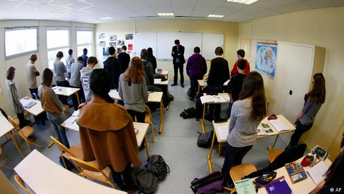 Unidentified pupils of the Anne-Franck college in Lambersart, northern France, and their class teacher Laurie Larvent, center, hold a minute of silence in their classroom on Tuesday, March 20, 2012, the day after a gunman on a motorbike opened fire Monday at a Jewish school in the French city of Toulouse, southwestern France, killing a rabbi and his two young sons as they waited for a bus, then chased down a 7-year-old girl, shooting her dead at point-blank range. It was the latest in a series of attacks on minorities that have raised fears of a racist killer on the loose. (Foto:Michel Spingler/AP/dapd)