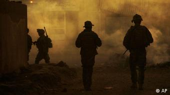 U.S. Army soldiers are seen through the haze of burning trash (AP Photo/Maya Alleruzzo)