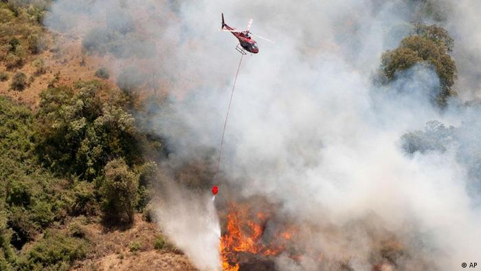 A helicopter from the Lady Lori charter company drops water from the air in an attempt to put out a fire on the slopes of Mount Kenya