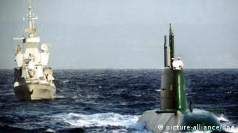 An Israeli navy boat escorts a German-made Israeli submarine