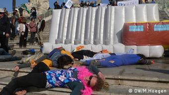 Demonstrators lay, as if dead, in front of inflatable dam