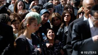 The mother of seven-year-old Miriam Monsonego (bottom center) mourns during the joint funeral service in Jerusalem for her daughter and the other three victims