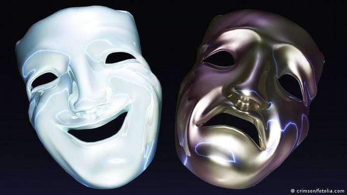 A white smiling mask next to a gray frowning mask.