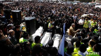 Mourners stand around the bodies of the victims of Monday's shooting in Toulouse during their joint funeral service in Jerusalem March 21, 2012. A gunman, suspected of killing three children and a rabbi at a Jewish school in the name of al Qaeda, said on Wednesday he would hand himself over to police after an hours-long siege in which he wounded three officers. REUTERS/Baz Ratner (JERUSALEM - Tags: POLITICS CIVIL UNREST)