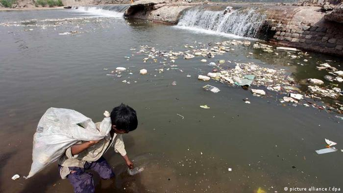 A young boy picks up a rag from a the polluted Tawi river