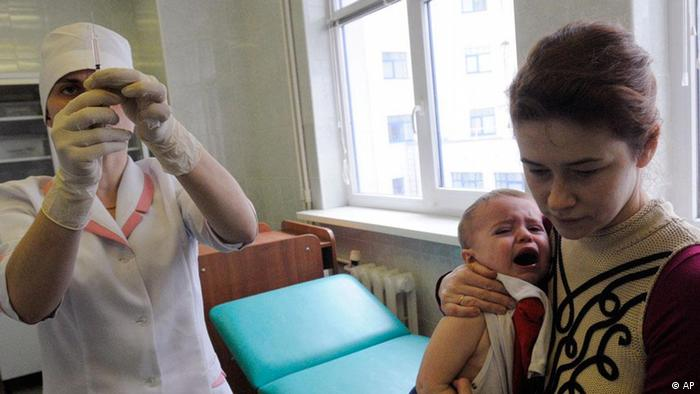 A medical worker prepares to administer a vaccine to Yaroslav, 16 month old, being held by his mother Oksana Vasylenko in a outpatient clinic in Kiev, Ukraine, Friday, March 20, 2009. A widespread scare about vaccine side effects in Ukraine has led to a sharp drop in immunizations that could result in disease outbreaks spreading beyond the former Soviet republic, international and local health officials say. Hundreds of thousands of fearful Ukrainians have refused vaccines for diseases such as diphtheria, mumps, polio, hepatitis B, tuberculosis, whooping cough and others this year, according to official estimates. Authorities have canceled a measles and rubella vaccination campaign funded by U.S. philanthropist Ted Turner, and will have to collect and incinerate nearly 9 million unused doses in coming months. (ddp images/AP Photo/Sergei Chuzavkov)
