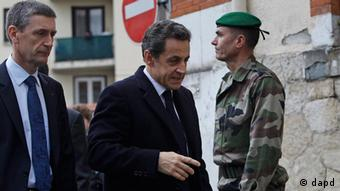 France's President Nicolas Sarkozy, center, flanked with Paris Prosecutor Francois Molins, left, arrive to meet soldiers and Police officers close to the apartment building where a suspect in the shooting at the Ozar Hatorah Jewish school is barricaded in Toulouse, Southern France, Wednesday, March 21, 2012. A predawn police raid on a home in Toulouse erupted into a firefight Wednesday with a gunman who claims connections to al-Qaida and is suspected of killing three Jewish schoolchildren, a rabbi and three paratroopers. (Foto:Christophe Ena/AP/dapd)