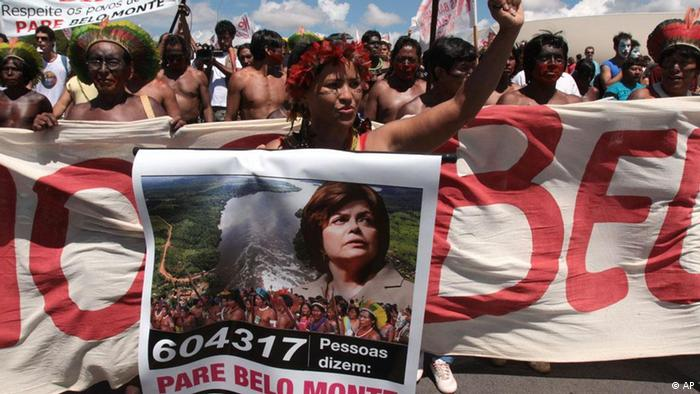 A member of the Kaiapo tribe holds a poster showing a picture of Brazil's President Dilma Rousseff during a protest by indigenous communities against the construction of Belo Monte hydroelectric dam in front the National Congress in Brasilia, Brazil, Tuesday Feb. 8, 2011. A Brazilian environmental agency has given approval for initial work to begin on a massive hydroelectric dam planned for the heart of the Amazon jungle. The 11,000-megawatt project to dam the Xingu River, which feeds the Amazon, would be the third-largest such hydroelectric project in the world. The poster reads Stop Belo Monte and the number 604,317 refers to the number of people they say have signed a petition against the project. (ddp images/AP Photo/Eraldo Peres)
