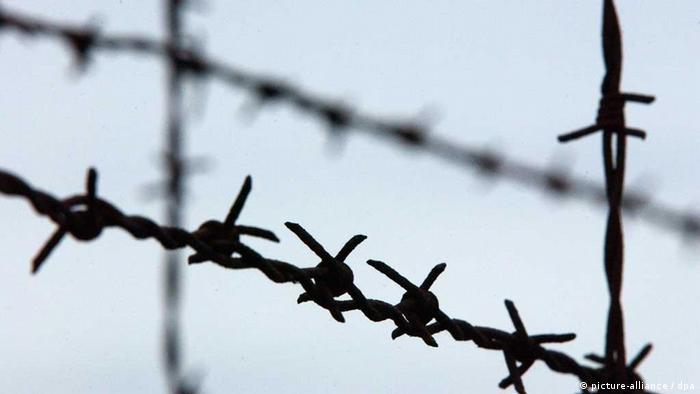 Stacheldrahtzaun im Konzentrationslager Dachau: Am 21. März 1933 gab Heinrich Himmler die Errichtung eines Konzentrationslagers in Dachau in Auftrag. Damit begann in Dachau ein Terrorsystem, das mit keinem anderen staatlichen Verfolgungs- und Strafsystem verglichen werden kann. Die ersten Häftlinge waren politische Gegner des Regimes, Kommunisten, Sozialdemokraten, Gewerkschafter, vereinzelt auch Mitglieder konservativer und liberaler Parteien. Auch die ersten jüdischen Häftlinge wurden auf Grund ihrer politischen Gegnerschaft in das Konzentrationslager Dachau eingeliefert. In den folgenden Jahren wurden immer neue Gruppen nach Dachau verschleppt: Juden, Homosexuelle, Zigeuner, Zeugen Jehovas, Geistliche u.a. Allein als Folge des Novemberpogroms, der sogenannten Reichskristallnacht, wurden mehr als 10.000 Juden in das Konzentrationslager Dachau gebracht. Insgesamt waren über 200.000 Häftlinge aus mehr als 30 Staaten in Dachau inhaftiert. (Foto vom 25.10.2002)
