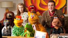 In this film publicity image released by Disney, Amy Adams, left, and Jason Segel are shown with the muppet characters in a scene from The Muppets. (AP Photo/Disney Enterprises, Patrick Wymore)