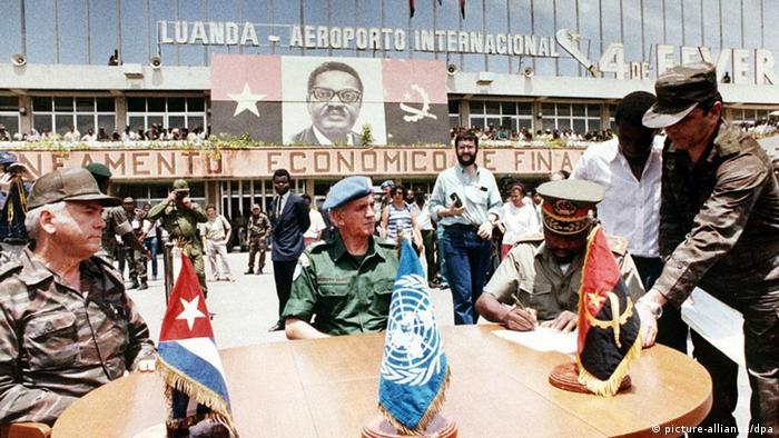 A retirada dos soldados cubanos permitiu avançar com a paz. Na foto: O general cubano, Samuel Rodiles, o general brasileiro e chefe da missão de verificação da retirada das tropas cubanas do território angolano da ONU, Péricles Ferreira Gomes, e o general angolano Ciel da Conceição assinam um documento sobre a retirada no dia 10 de janeiro de 1989 no Aeroporto de Luanda