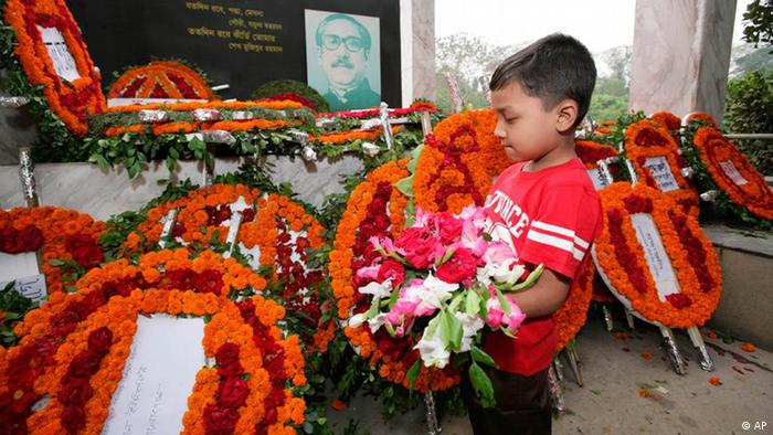 A Bangladeshi boy places a bouquet before a portrait of country's independence leader Sheikh Mujibur Rahman at Dhanmondi in Dhaka, Bangladesh, Thursday, March 26, 2009. Bangladeshis celebrated 38 years of independence Thursday amid tight security as tens of thousands of people visited a national memorial outside the capital to mark the split from Pakistan in which millions of people died. (AP Photo/Pavel Rahman)