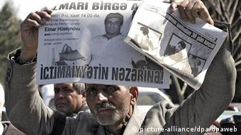 An elderly Azeri man displays a newspaper with a portrait of a journalist killed 02 march