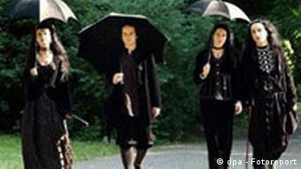 Vier Gothik-Anhänger laufen schwarz bekleidet einen Weg entlang