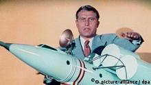 Der US-amerikanische Raketenkonstrukteur deutscher Herkunft erklärt die Funktion eines Raketen-Raumschiffs an einem Modell. Wernher Freiherr von Braun leitete im Zweiten Weltkrieg die Entwicklung der V-2 Rakete in Peenemünde. Er siedelte 1945 in die USA über, wo er 1955 US-amerikanischer Staatsbürger wurde und bis zum stellvertretenden Direktor der US-Raumfahrtbehörde NASA (ab 1970) aufstieg. Undatierte Aufnahme.