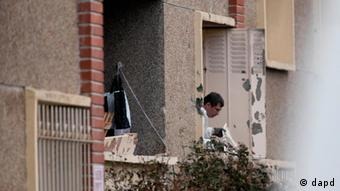 A French police officer is seen at the window of Mohamed Merah's apartment, after a suspect, wanted in the deaths of three paratroopers, three Jewish schoolchildren and a rabbi, died following a standoff with police, Toulouse, France, Thursday, March 22, 2012. Mohamed Merah, who boasted of killing seven people to strike back at France died after being shot in the head by police as he jumped out of his apartment after a fierce gunfight with police, authorities said. (AP Photo / Thibault Camus)