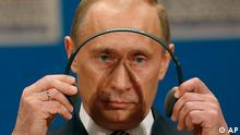 Russian President Vladimir Putin dons his headphones during a press conference on the third day of the NATO Summit conference in Bucharest, Friday April 4 2008. Putin told reporters that he thinks Friday's session with U.S. President George W. Bush and other leaders was positive - even though Moscow fiercely opposed the alliance's effort to put Ukraine and Georgia on track for NATO membership.(AP Photo/Vadim Ghirda)