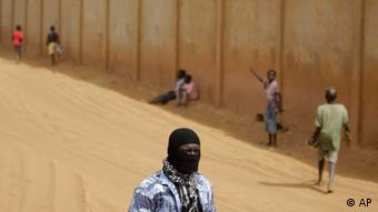 A security agent for Senegalese President Abdoulaye Wade wears a balaclava as he stands watch while Wade tours downtrodden suburban areas outside Dakar, Senegal Wednesday, March 21, 2012, ahead of Senegal's presidential run-off election. Senegal's aging leader will face his former protege Macky Sall in a runoff election on Sunday, March 25. Opposition leaders have united behind Sall in an effort to put an end to Wade's bid for a controversial third term as president. (Foto:Rebecca Blackwell/AP/dapd)