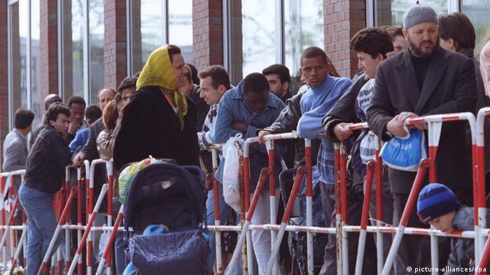 شمالی جرمن شہری ریاست ہیمبرگ میں غیر ملکیوں سے متعلقہ امور کے ایک مقامی دفتر کے باہر قطار بنائے پناہ کے متلاشی تارکین وطن