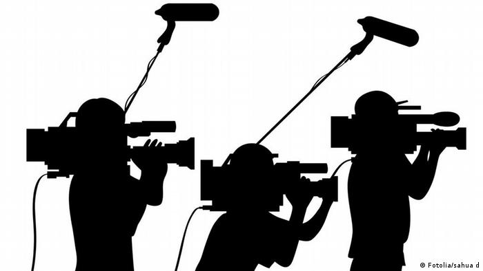 Cameraman at work silhouettes side view (photo: sahua)