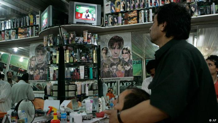 An Afghan barber watches the presidential candidates' debate on television at his shop in Kabul, Afghanistan, Thursday, July 23, 2009.Two leading candidates in the Aug. 20 presidential election faced one another in an unprecedented television debate _ which went ahead despite a decision by President Hamid Karzai not to take part. Former foreign minister Abdullah Abdullah and ex-finance minister Ashraf Ghani both cited civilian casualties, searching private homes without permission and arresting people without cause as major reasons for opposition to the presence of U.S. and other international forces. (ddp images/AP Photo/Rafiq Maqbool).