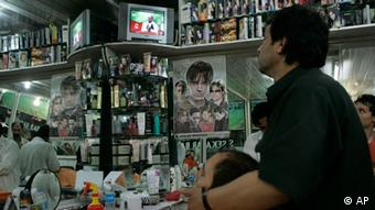 An Afghan barber watches television