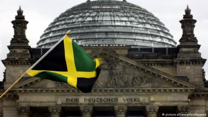 A Jamaican flag waves in front of Germany's parliament. The colors of the flag represent a coalition between the CDU, whose color is black, the FDP, whose color is yellow, and Green, for the Greens Party.