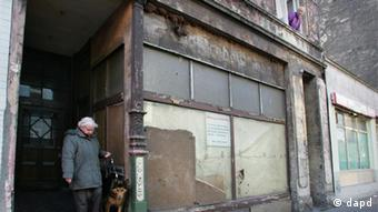 An old lady and her dog leaving her very run-down home in Duisburg-Bruckhausen in the Ruhr. The windows on the ground floor of the building are boarded up. (Photo: Torsten Silz/dapd)