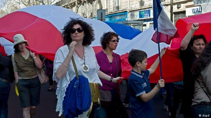 Demonstrators hold a giant French flag as they attend a march in memory of the victims of Mohamed Merah, in Los franceses marcharon contra el racismo el pasado fin de semana.