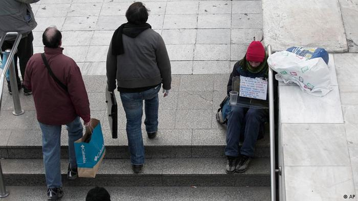 Pedestrians walking past homless beggar at Athens' main Syntagma square