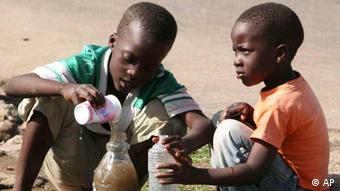 Two children collecting stagnant water in a plastic bottle
