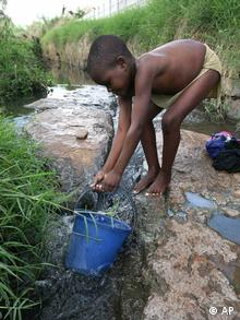 A young boy fetches water in Zimbabwe