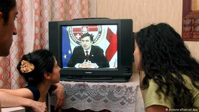 Residents of Tbilisi watch on TV President Mikheil Saakashvili addressing the Georgian people
