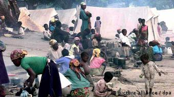 Women and children sit around waiting for food distribution in a refugee camp at San Joao, near Huambo, in 1999.