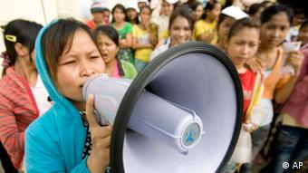 A Cambodian garment worker speaks on a loud speaker as she leads a strike in front of a factory on the outskirts of Phnom Penh, Cambodia, Monday, Sept. 13, 2010. (AP Photo/Heng Sinith)