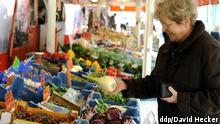 ältere Frau kauft Gemüse auf dem Markt