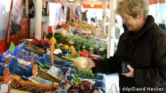 Žena na tržnici gleda povrće