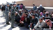 Schwere Zeiten für Flüchtlinge in Italien auf Lampedusa.jpg Illegale Immigranten auf der Insel Lampedusa (Archivbild vom 15.03.2005). Seit fast einem Jahr hat Italien auf Anordnung von Innenminister Giuseppe Pisanu damit begonnen, zahlreiche Immigranten gleich wieder auszufliegen. Nun werden Vorwürfe laut, dass in den Auffanglagern Zustände wie im viel kritisierten US-Hochsicherheitsgefängnis Guantànamo auf Kuba herrschten. Ein Journlist, der sich als vermeindlicher Flüchtling in ein Lager geschmuggelt hatte, berichtet von menschenunwürdigen hygienischen Zuständen und von Schlägen. EPA/FRANCO LANNINO (zu dpa-KORR: 'Wie in Guantànamo' - Schwere Zeiten für Flüchtlinge in Italien vom 09.10.2005) +++(c) dpa - Bildfunk+++ Für projekt Destination Europe Leben im Auffanglager