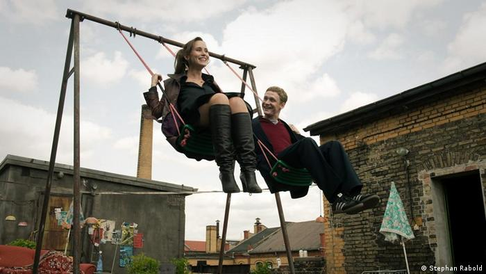 A still from the film Russian Disco: Two people on a swing, smiling, Berlin buildings in the background