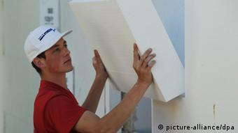Строительный рабочий с пенополистирольной плитой