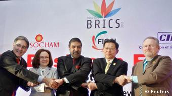 Brazilian Trade Minister Fernando Pimentel (L-R), Russia's Economic Development Minister Elvira Nabiullina, India's Trade Minister Anand Sharma, China's Minister of Commerce Chen Deming and South African Minister of Trade and Industry Rob Davies, shake hands during a group photograph at the BRICS Summit Forum themed BRICS Partnership for Stability, Security and Growth in New Delhi March 28, 2012. The BRICS group of emerging world powerhouses - Brazil, Russia, India, China and South Africa - is expected to launch plans this week for a joint development bank and measures to bring their stock exchanges closer together. REUTERS/Vijay Mathur (INDIA - Tags: POLITICS BUSINESS)