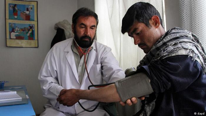 Afghan doctor Mohammad Daoud Aslami checks the pressure of a patient at a health center in Kabul, Afghanistan (ddp images/AP Photo/Musadeq Sadeq)