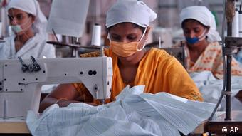 Bangladeshi garments workers stitch at a factory in Dhaka, Bangladesh, Thursday, Nov.10, 2005.