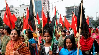 Bangladeshi garments workers carry red and black flag as they protest the killing of their fellow workers in Dhaka, Bangladesh, Tuesday, Nov. 10, 2009. (Photo: AP)