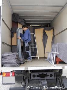 Ein Möbelpacker arrangiert in einem Umzugs-LKW Sachen