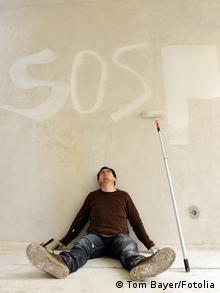 Ein Mann sitzt völlig erschöpft auf dem Boden, neben sich eine Stange zum Anstreichen und den Buchstaben SOS über sich