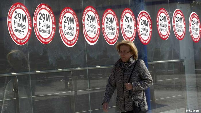 A woman walks past a subway station with stickers announcing a general strike called by Spain's unions in Madrid March 28, 2012. Train, bus and air traffic will be severely limited in Spain on Thursday during a general strike called by unions to protest high unemployment and changes to labour laws that will make it cheaper for companies to lay off employees. The unions, which represent one in five Spanish workers, and the government agreed to retain minimum transport services for Thursday, including only 20 percent of flights between Spanish and other European airports. REUTERS/Sergio Perez (SPAIN - Tags: BUSINESS EMPLOYMENT POLITICS CIVIL UNREST) // Eingestellt von wa