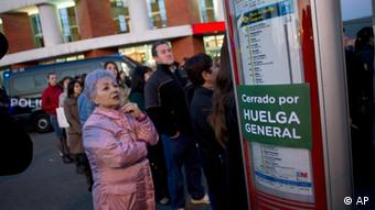 People stand and wait for a bus at Atocha Station in Madrid, Spain, Thursday, March 29, 2012 during a general strike. The one-day trade union sponsored general strike is protesting changes to labor market rules long regarded as among Europe's most rigid that include making it cheaper and easier for companies to lay people off and cutting wages. The banner on the bus stop reads 'Closed because of General Strike'. (Foto:Alberto Di Lolli/AP/dapd)